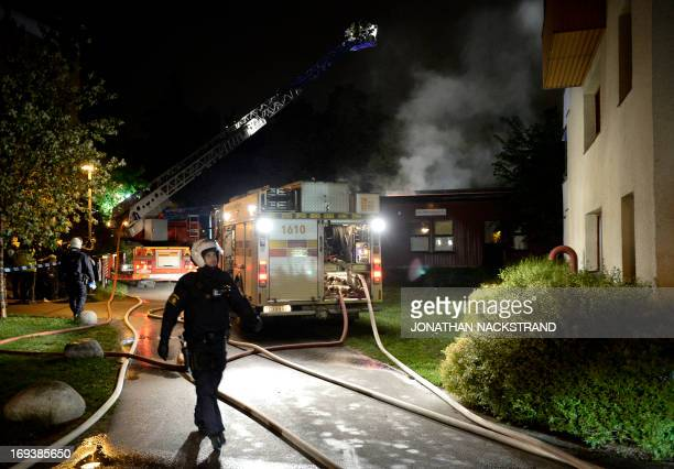 Police force secure the area where firemen extinguish a nursery school in the Stockholm suburb of Kista after youths rioted in several different...