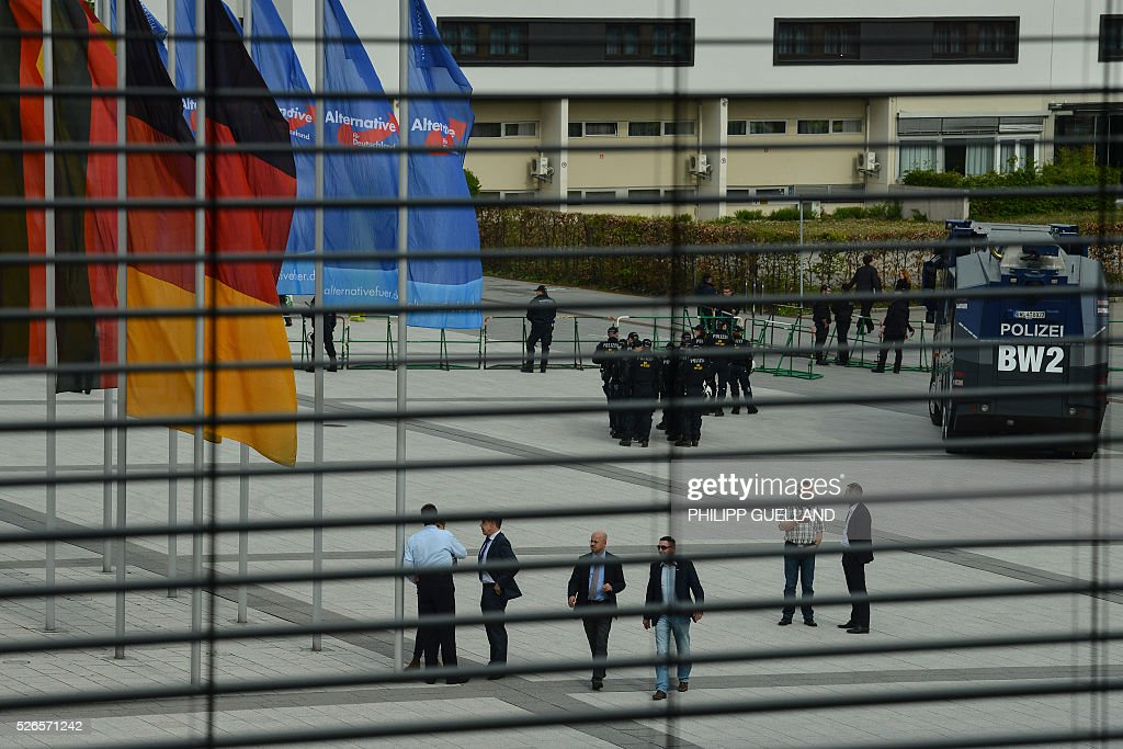 Police forces and delegates are seen in front of the venue of the german right wing party Alternative for Germany (AfD) at the the Stuttgart Congress Centre ICS on April 30, 2016. The Alternative for Germany (AfD) party is meeting in the western city of Stuttgart, where it is expected to adopt an anti-Islamic manifesto, emboldened by the rise of European anti-migrant groups like Austria's Freedom Party. / AFP / Philipp GUELLAND