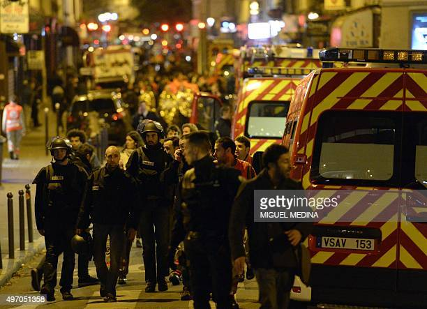 Police forces and rescuers walk through rue Oberkampf near the Bataclan concert hall in central Paris early on November 14 2015 At least 120 people...