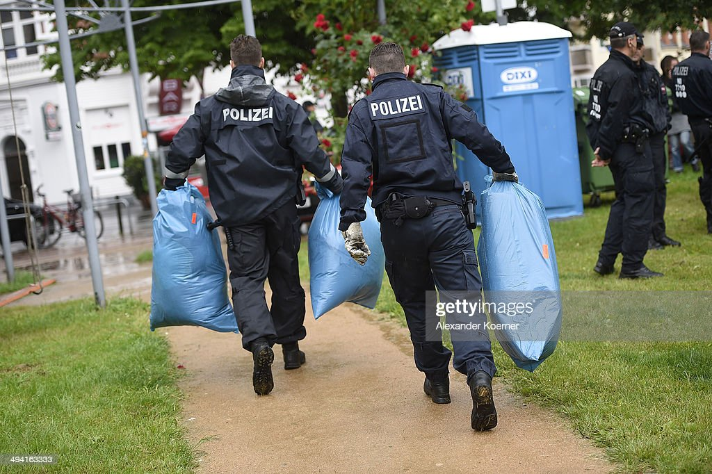 Police forces carry blue bags with dismantled tents inside, which were set up illegally by African migrants on the White Cross Square (Weissekreuzplatz) in the Oststadt district on May 28, 2014 in Hanover, Germany. Around 30 African migrants and 20 supporters had setup the protest camp on Saturday to protest against the asylum policy of the German Federal Republic and call for fair and equal treatment of all asylum seekers. The Police operation was completed peacefully.