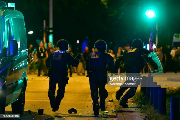 Police forces chase leftwing protestors after erecting burning barricades in front of the Rote Flora leftwing centre during a march on July 7 2017 in...