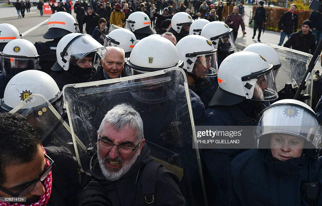 Police forces escort a party member past protesters to a party congress of the German right wing party AfD (Alternative fuer Deutschland) at the Stuttgart Congress Centre ICS on April 30, 2016 in Stuttgart, southern Germany. Protesters tried to block the access to the party conference of the 'Alternative Fuer Deutschland' (Alternative for Germany) with around 400 being taken into custody. / AFP / Philipp GUELLAND