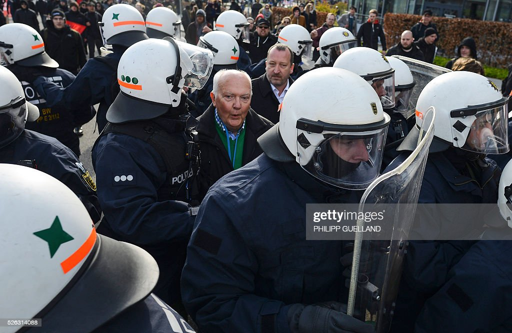 Police forces escort a party member (C) to a party congress of the German right wing party AfD (Alternative fuer Deutschland) at the Stuttgart Congress Centre ICS on April 30, 2016 in Stuttgart, southern Germany. Protesters tried to block the access to the party conference of the 'Alternative Fuer Deutschland' (Alternative for Germany) with around 400 being taken into custody. / AFP / Philipp GUELLAND