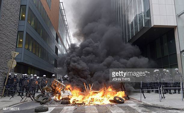 Police forces face a fire lit by participants of a farmers demonstration in front of the European Commission building on September 7 in Brussels as...