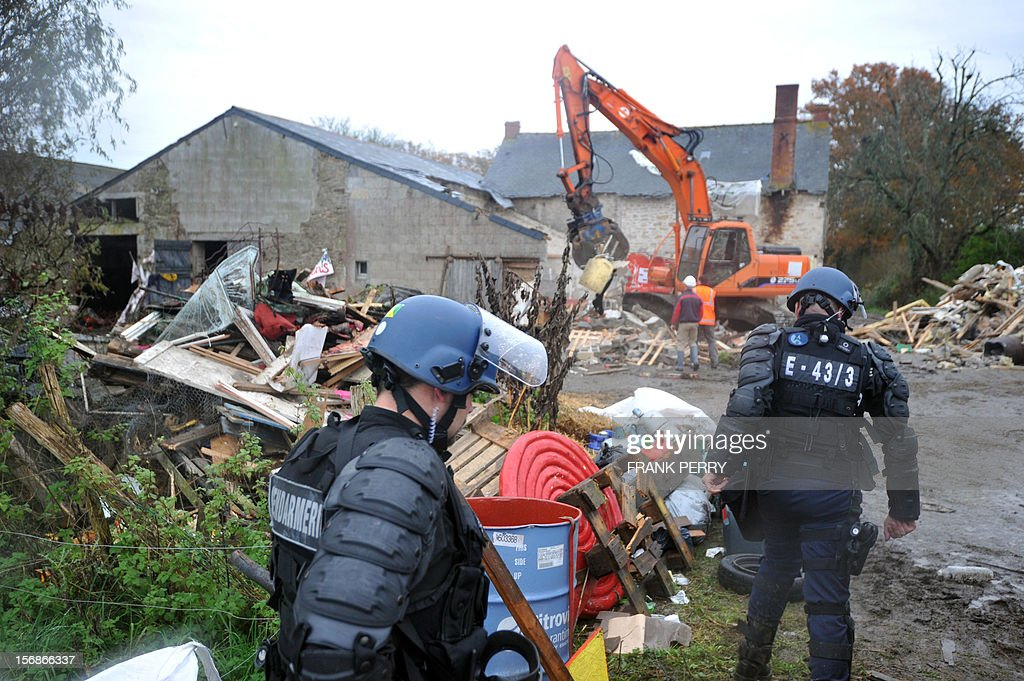 Police forces look at a steam shovel destroying the farm squatted by protestors against a project to build an international airport, following its evacuation, on November 23, 2012 in Notre-Dame-des-Landes, western France. The battle led by opponents against the airport is also judicial, with multiple legal recourses ongoing. The project was signed in 2010 and the international airport is supposed to open in 2017 near the city of Nantes.