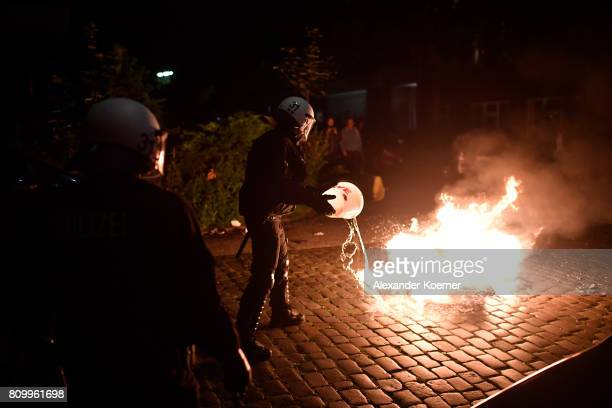Police forces put out a small fire after protestors erected burning barricades in front of the Rote Flora leftwing centre during a march on July 7...