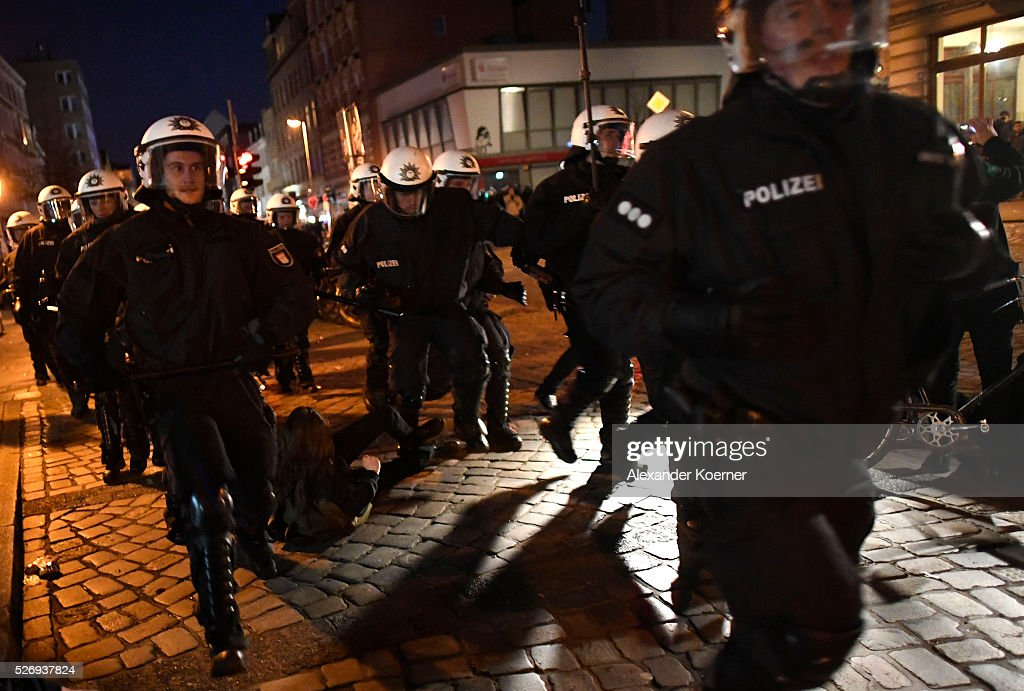 Police forces run by an injured left wing protester on the ground after clashes occured at 'Rote Flora' on May Day on May 01, 2016 in Hamburg, Germany. Tens of thousands of people across Germany participated in marches and gatherings by labor unions and in some cities left-wing and anarchist activists took to the streets under heavy oversight by police.