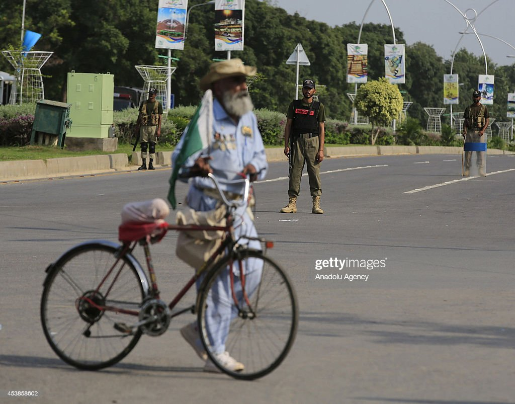 Police forces stand guard as followers of the Pakistan Tehreek-e-Insaf (PTI) and the Pakistan Awami Tehreek (PAT) parties enter Pakistani capital Islamabad's sensitive Red Zone area, which houses state buildings, on August 20, 2014. Thousands of protesters loyal to opposition politician Imran Khan and religious scholar Dr Tahir-ul-Qadri started their march on the parliament house after the two leaders asked their supporters to enter the Red Zone, a heavily protected area where many official and diplomatic buildings are located.