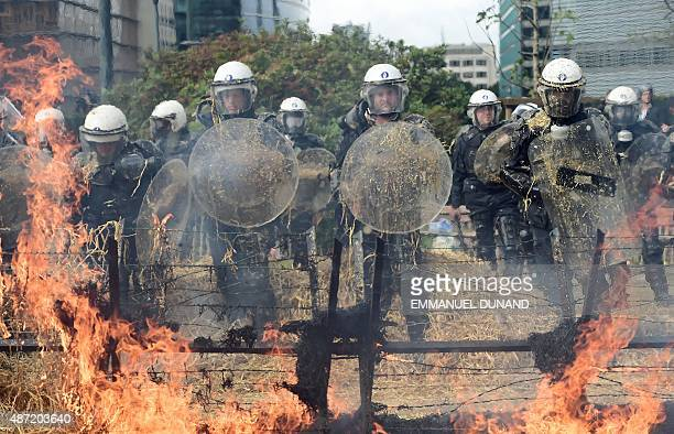 Police forces stand in front of fires lit by protestors after receiving eggs and straws during a farmers demonstration in front of the European...