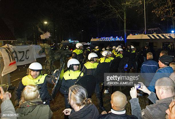 Police forces stand in front of protestors during a demonstration on December 16 2015 at a council meeting about plans to open a refugee centre for...