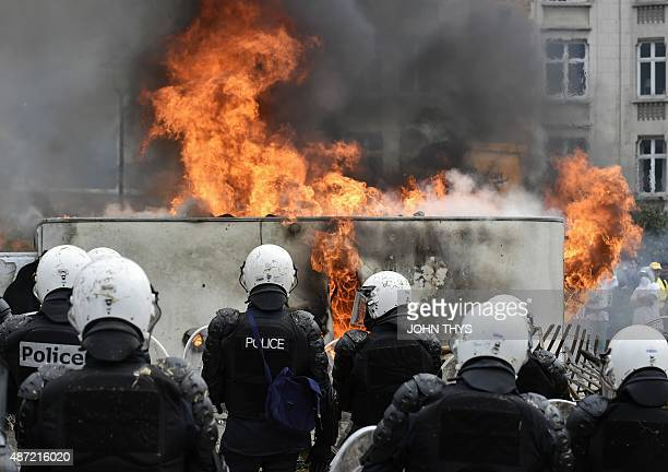 Police forces stand next to a car fire during a demonstration of farmers on September 7 2015 in Brussels as European agriculture ministers hold an...