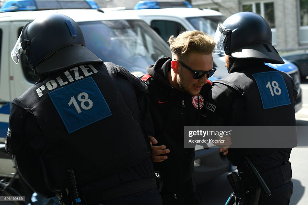 Police forces take a fan of Eintrach Frankfurt into custody prior the Bundesliga Match of SV Darmstadt 98 and Eintracht Frankfurt at 'Merck-Stadion am Boellernfalltor' on April 30, 2016 in Darmstadt, Germany. Fans of Eintracht Frankfurt burnt scarves and banners during the first leg game in December 2015 of SV Darmstadt 98. The city of Darmstadt has rejected a ban of staying for fans of Eintracht Frankfurt for 36 hours inside the city centre and the stadium during the morning hours.