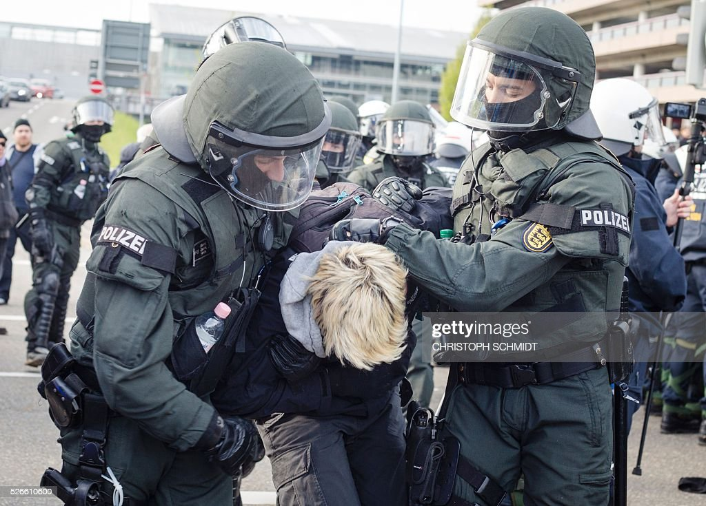 Police forces take a protestor into custody during a demonstration against a party congress of the German right wing party AfD (Alternative fuer Deutschland) at the Stuttgart Congress Centre ICS on April 30, 2016 in Stuttgart, southern Germany. Protesters tried to block the access to the party conference of the 'Alternative Fuer Deutschland' (Alternative for Germany) with around 400 being taken into custody. / AFP / dpa / Christoph Schmidt / Germany OUT