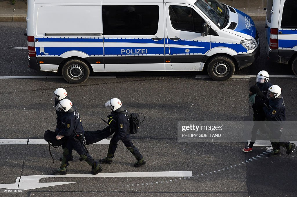 Police forces take protesters into custody during a demonstration against a party congress of the German right wing party AfD (Alternative fuer Deutschland) at the Stuttgart Congress Centre ICS on April 30, 2016 in Stuttgart, southern Germany. Protesters tried to block the access to the party conference of the 'Alternative Fuer Deutschland' (Alternative for Germany) with around 400 being taken into custody. / AFP / Philipp GUELLAND