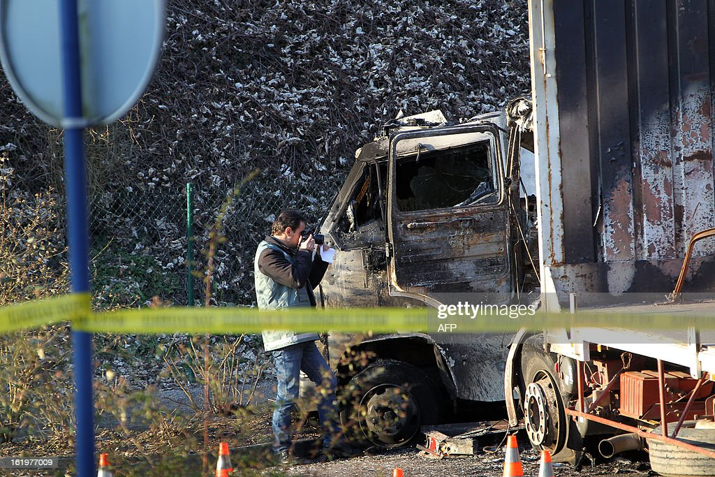 A Police forensic expert takes pictures of a burnt cash-in-transit (CIT) vehicle (C) after an attack in Bois-Guillaume, near Rouen, northwestern France, on February 18, 2013. Criminals have hit the Loomis van with a 19 tons truck (R). Two CIT security staff were slightly injured. AFP PHOTO/CHARLY TRIBALLEAU