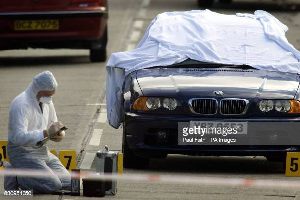 Police forensic experts examine the area rond a BMW car in Newtownards Co Down Northern Ireland afther a was man killed in a driveby shooting that...