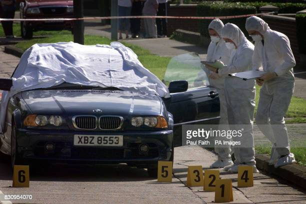 Police forensic experts examine the area surrounding a BMW car in Newtownards Co Down Northern Ireland A man was killed in a driveby shooting in what...