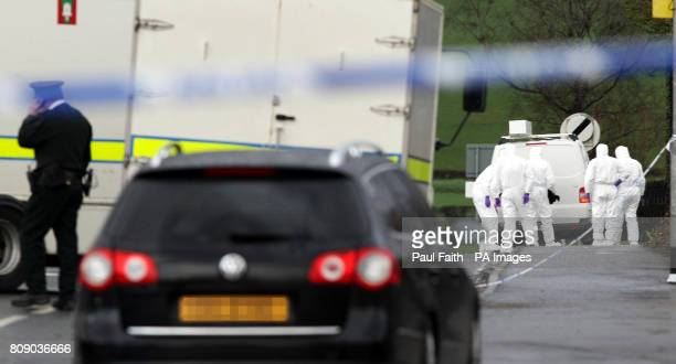 Police forensic experts move into examine the area where a policeman was killed in an under car booby trap explosion in Omagh Co Tyrone today