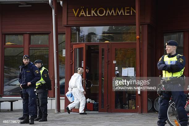 A police forensic officer enters a primary and middle school in Trollhattan southwestern Sweden on October 22 where a masked man armed with a sword...