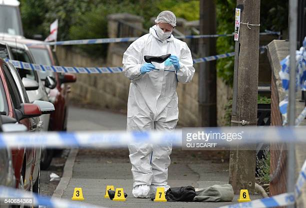 A police forensic officer picks up a shoe from the crime scene on the pavement outside the library in Birstall northern England where Labour MP Jo...