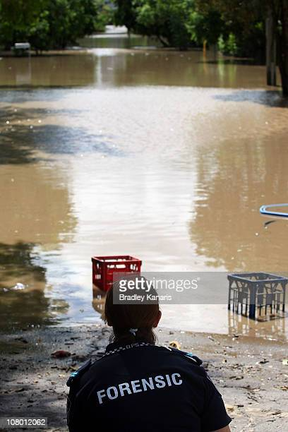 Police forensic officer takes photos of Ryan Street in the suburb of West End on January 13 2011 in Brisbane Australia The Brisbane river peaked at...