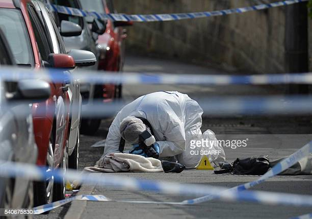 A police forensic officer works at the scene where a coat shoe and handbag lie on the pavement outside the library in Birstall where Labour MP Jo Cox...