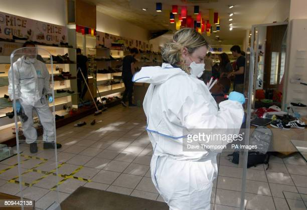 Police forensic officers gather evidence at an Office shoe shop in St Ann's Square in Manchester after rioting in the city centre last night