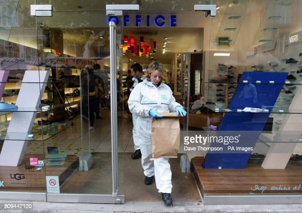Police forensic officers leave an Office shoe shop in St Ann's Square in Manchester after rioting in the city centre last night