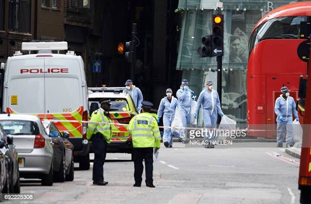 Police forensic officers work on road inbetween Borough Market and London Bridge in London on June 4 as police continue their investigations...