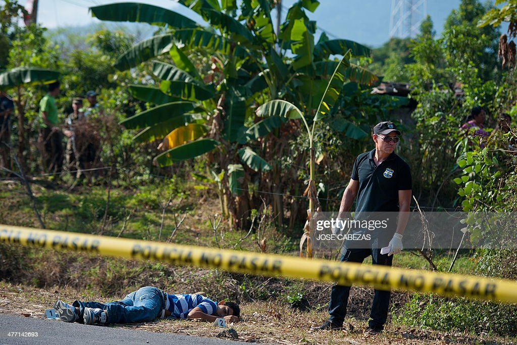 A police forensic works on a murder scene where an alleged gang member was killed in the town of Nejapa, 24 km north from San Salvador, El Salvador on March 7, 2014 prior to the second round of the presidential elections to be held on March 9. AFP PHOTO/ Jose CABEZAS