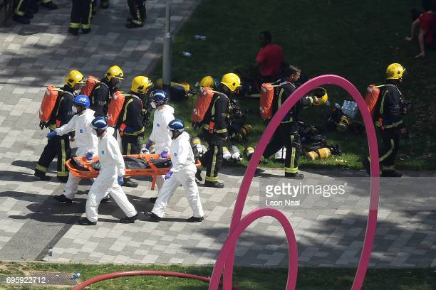 Police forensics carry a stretcher with a body bag out of the 24 storey residential Grenfell Tower block as fire crews make their way back in at...