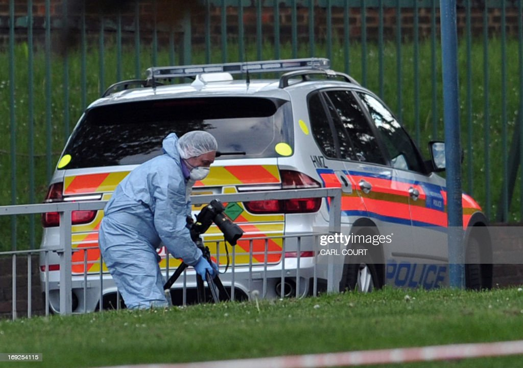 A police forensics officer takes photographs inside a cordoned off area in Woolwich, east London, on May 22, 2013, following an incident in which one man was killed and two others seruiously injured. British police shot and wounded two men after a man thought to be a serving soldier was killed outside a London barracks, in an attack Prime Minister David Cameron called 'truly shocking'. In a dramatic move, the government's emergency response committee was being summoned following the killing which some eyewitness reports suggested was an attempted beheading using machete-like knives.