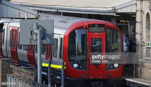 A police forensics officer works alongside an underground tube train at a platform at Parsons Green underground tube station in west London on...