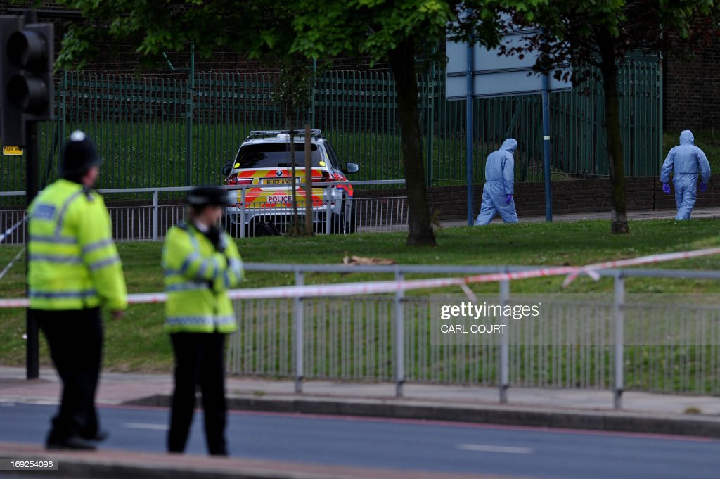 Police forensics officers search a cordoned off area in Woolwich, east London, on May 22, 2013, following an incident in which one man was killed and two others seruiously injured. British police shot and wounded two men after a man thought to be a serving soldier was killed outside a London barracks, in an attack Prime Minister David Cameron called 'truly shocking'. In a dramatic move, the government's emergency response committee was being summoned following the killing which some eyewitness reports suggested was an attempted beheading using machete-like knives.