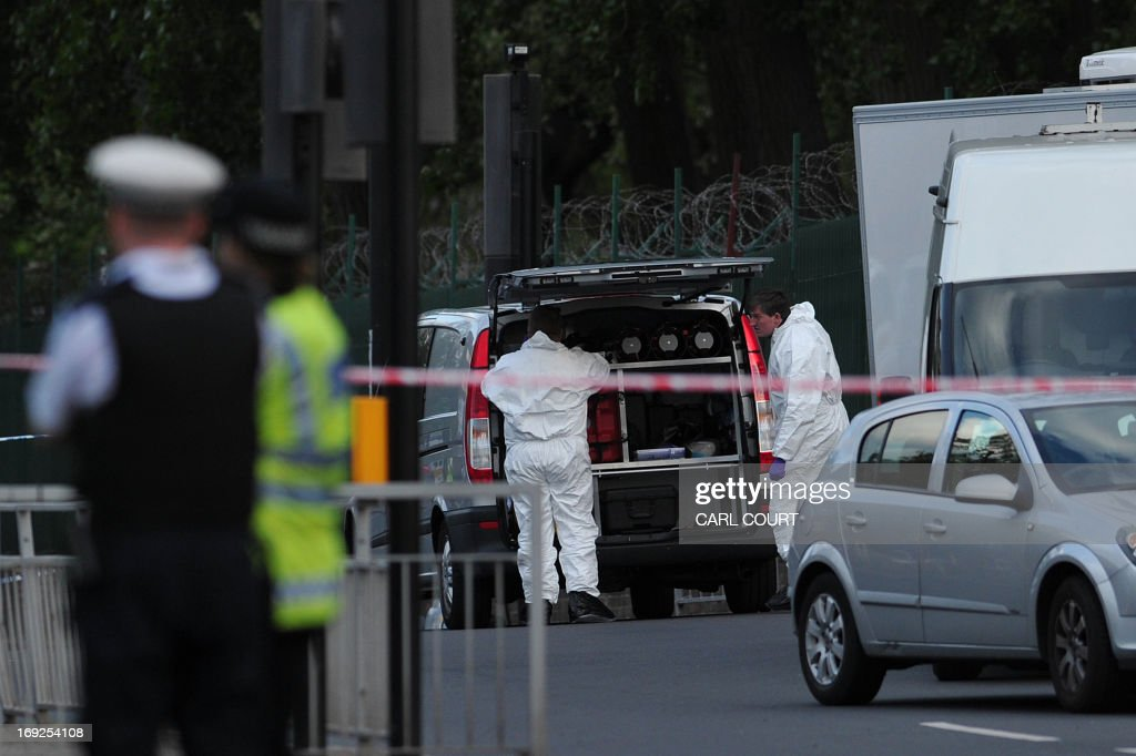 Police forensics officers search a cordoned off area in Woolwich, east London, on May 22, 2013, following an incident in which one man was killed and two others seruiously injured. British police shot and wounded two men after a man thought to be a serving soldier was killed outside a London barracks, in an attack Prime Minister David Cameron called 'truly shocking'. In a dramatic move, the government's emergency response committee was being summoned following the killing which some eyewitness reports suggested was an attempted beheading using machete-like knives. AFP PHOTO / CARL COURT