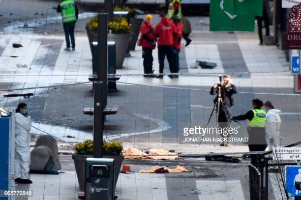 Police forensics officers work at the scene where a truck crashed into the Ahlens department store at Drottninggatan in central Stockholm April 7...