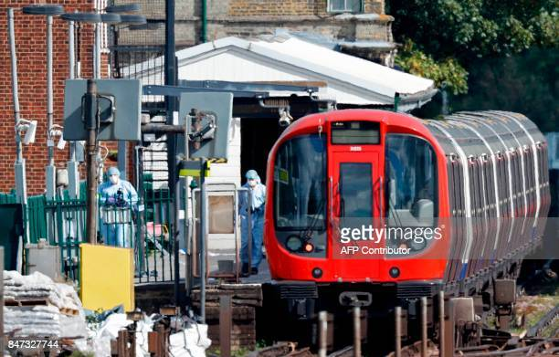 TOPSHOT Police forensics officers works alongside an underground tube train at a platform at Parsons Green underground tube station in west London on...