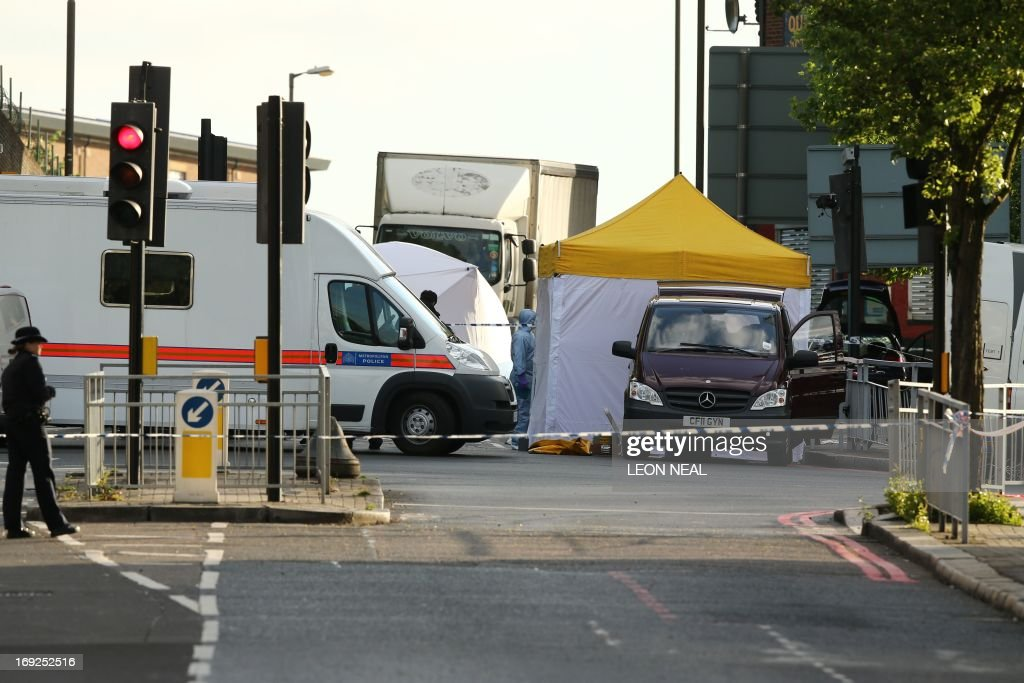 Police forensics tents and officers are seen in Woolwich, east London, on May 22, 2013. British police shot and wounded two men after a man thought to be a serving soldier was killed outside a London barracks, in an attack Prime Minister David Cameron called 'truly shocking'. In a dramatic move, the government's emergency response committee was being summoned following the killing which some eyewitness reports suggested was an attempted beheading using machete-like knives. AFP PHOTO/Leon Neal