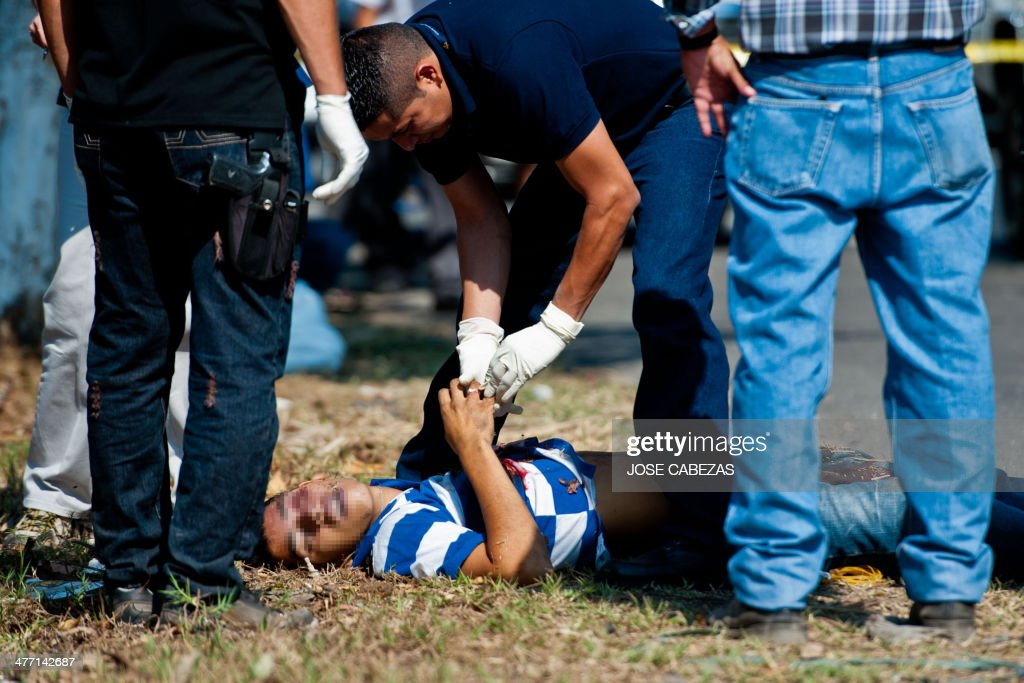 Police forensics work on a murder scene where an alleged gang member was killed in the town of Nejapa, 24 km north from San Salvador, El Salvador on March 7, 2014 prior to the second round of the presidential elections to be held on March 9. AFP PHOTO/ Jose CABEZAS