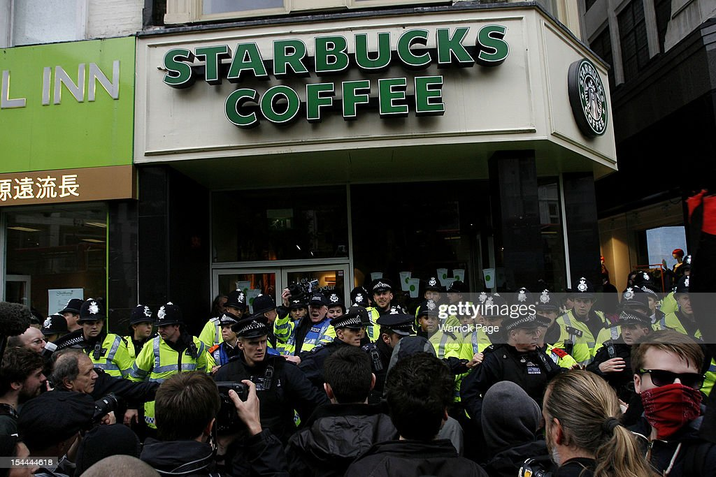 Police form a line outside a Starbucks coffee shop as deomstrators participate in a protest against the government's austerity measures targeting several businesses on October 20, 2012 in London, England. Thousands of TUC members took part in a march against the government's austerity measures through London today which ended with a rally in Hyde Park, where Labour leader Ed Miliband addressed the demonstrators.