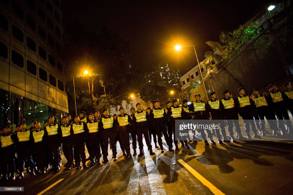 Police form a line to prevent protestors from reaching the front gate of government house, during a protest against embattled Hong Kong Chief Executive Leung Chun-ying, on January 1, 2013 in Hong Kong, Hong Kong. According reports, tens of thousands of protestors took to the streets demanding greater democracy 15 years after returning to Chinese rule.
