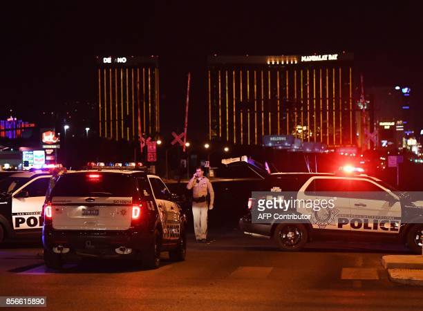 Police form a perimeter around the road leading to the Mandalay Hotel after a gunman killed at least 50 people and wounded more than 200 others when...