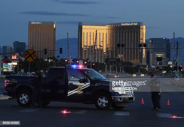 Police form a perimeter around the road leading to the Mandalay Hotel after a gunman killed at least 50 people and wounded more than 400 others when...