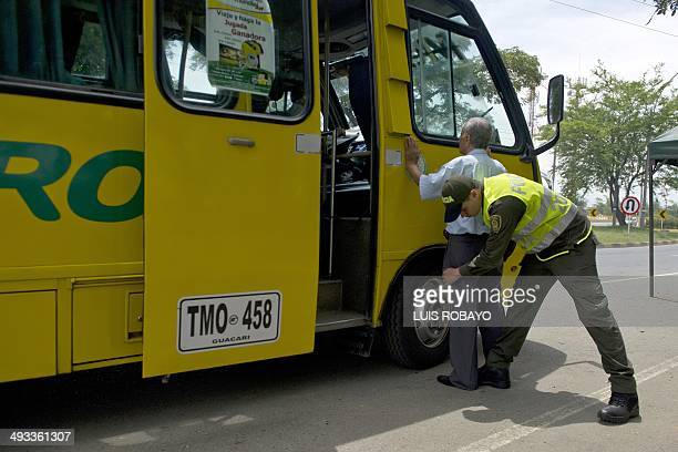 Police frisk passengers traveling on a bus in Cali Colombia on May 23 2014 Colombia's presidential elections will be held on May 25 AFP PHOTO / LUIS...