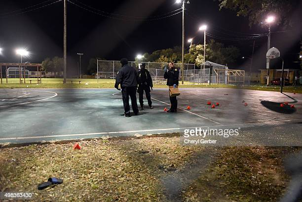 Police gather evidence after a shooting at a playground on November 22 2015 in New Orleans Louisiana According to reports as many as 16 people were...