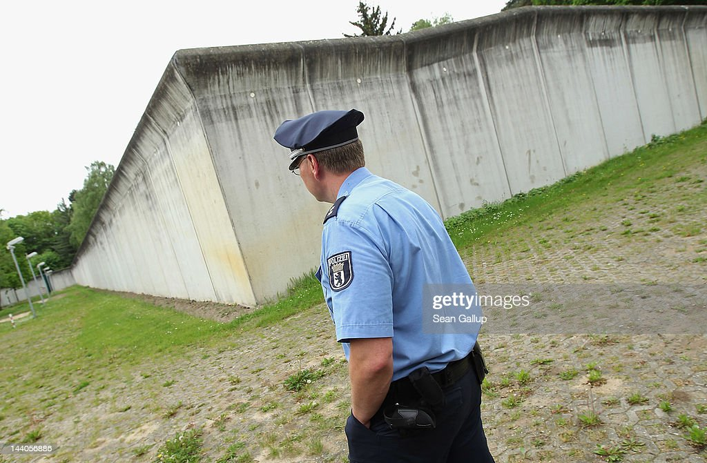 A police gaurd walks past the main wall at the expanded youth arrest facility in Lichtenrade district on May 9, 2012 in Berlin, Germany. The facility, whose capacity is now nearly doubled, accomodates young men and women first-time offenders for short periods of time with the intent of giving them an impression of what prison is like yet to also give them a second chance at returning to freedom.