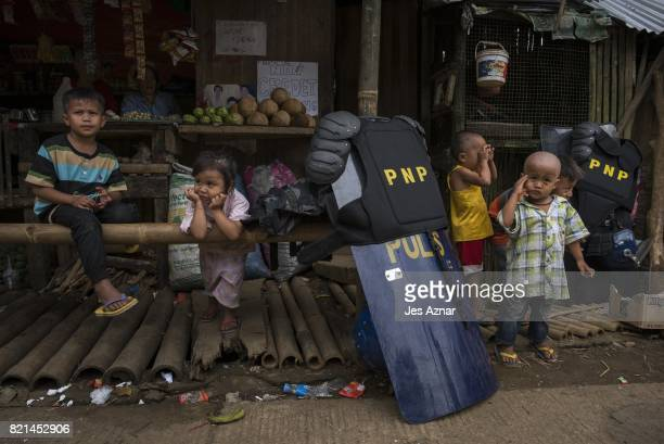 Police gear and shields are placed near playing displaced Marawi children on July 24 in Saguiaran Lanao del Sur southern Philippines Evacuees report...