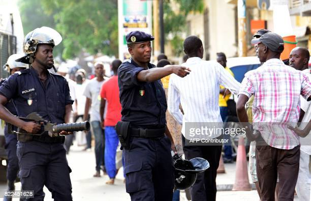 Police gesture to people near Independence Square in Dakar on July 25 2017 as they disperse supporters of the former Senegalese president gathered...