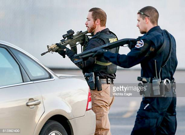 Police go through the parking lot of Excel Industries in Hesston Kan where a gunman reportedly killed up to seven people and injured many others on...