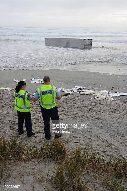 Police guard a container washed up on the beach on October 13 2011 in Tauranga New Zealand Up to 350 tonnes of oil has spilled from the 'Rena' a...